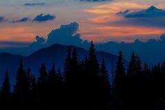 Восход солнца в горах Планы елевых верхних частей и лучей ` s солнца делают их путь через пики облаков Справочная информация Coni Стоковые Изображения