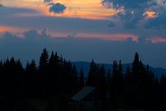 Восход солнца в горах Планы елевых верхних частей и лучей ` s солнца делают их путь через пики облаков Справочная информация Coni Стоковая Фотография