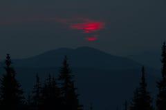 Восход солнца в горах Планы елевых верхних частей и лучей ` s солнца делают их путь через пики облаков Справочная информация Coni Стоковые Изображения RF