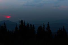 Восход солнца в горах Планы елевых верхних частей и лучей ` s солнца делают их путь через пики облаков Справочная информация Стоковое Изображение RF
