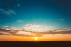 Восход солнца захода солнца над полем или лугом Яркое драматическое небо и Dar Стоковое Изображение