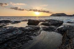 Восход солнца на море с скалистым пляжем Стоковое Изображение