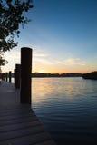 Восход солнца на стыковке шлюпки с штабелевками шлюпки Стоковые Изображения