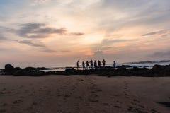 Восход солнца океана пляжа девушек Silhouetted мальчиками Стоковые Фотографии RF