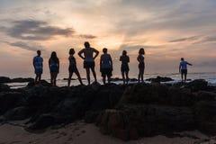 Восход солнца океана пляжа девушек Silhouetted мальчиками Стоковые Фото