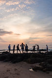 Восход солнца океана пляжа девушек Silhouetted мальчиками Стоковое фото RF