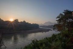 Восход солнца с золотыми лучами над рекой Luang Prabang стоковые изображения rf