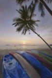 Восход солнца с пальмами шлюпки и кокоса каяка на тропической предпосылке пляжа Стоковая Фотография