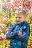 Восьмилетний мальчик стоит среди зацветая Сакуры в лучах захода солнца стоковое фото rf