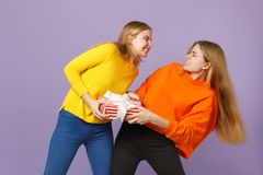2 воюя белокурых девушки сестер близнецов в ярких одеждах держат красную striped присутствующую коробку с лентой подарка изолиров стоковые изображения rf