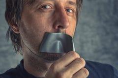 Воюя цензура, человек извлекая клейкая лента для герметизации трубопроводов отопления и вентиляции от рта Стоковое фото RF