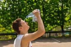 Вода атлетического человека лить от бутылки на сторону стоковое фото rf