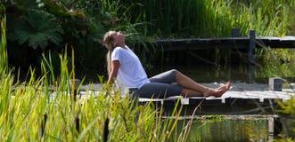 вода белокурой девушки 20s расслабляющая близко на понтоне Стоковая Фотография