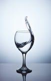 Вода брызгая из высокорослого бокала Стоковые Изображения