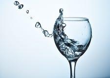 Вода брызгая из высокорослого бокала Стоковое Изображение RF