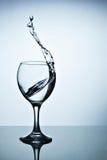 Вода брызгая из высокорослого бокала Стоковая Фотография RF