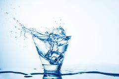 Вода брызгая от изолированного стекла на белизне Стоковые Изображения