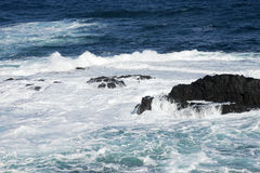 Вода, волны разбивая над утесами Стоковые Изображения