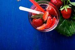 Вода вытрезвителя мяты клубники в стекле на голубой предпосылке Диета Взгляд сверху Стоковые Фотографии RF