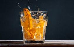 Вода вытрезвителя освежения с оранжевым коктеилем с воздушными пузырями и выплеск на черной предпосылке бетонной стены Стоковое Изображение