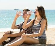 Вода в бутылках человека и женщины выпивая Стоковая Фотография
