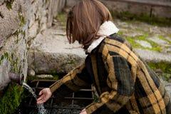Вода девушки касающая от естественного фонтана стоковое изображение rf