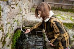 Вода девушки касающая от естественного фонтана стоковые изображения rf