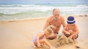 Вода замка песка строения мальчика девушки Grandpa моет вне видеоматериал