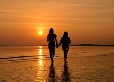 вода захода солнца силуэта друзей Стоковое фото RF
