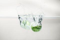 Вода зеленого яблока падая на белой предпосылке Стоковое Изображение RF