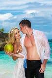 Вода кокоса питья жениха и невеста на тропическом пляже Стоковое Изображение