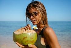 Вода кокоса привлекательной женщины выпивая на пляже Стоковые Фото