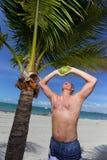 Вода кокоса человека выпивая на пляже Стоковые Фотографии RF
