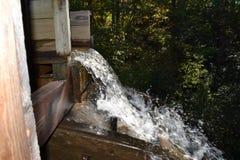 Вода падая от деревянного troth Стоковая Фотография