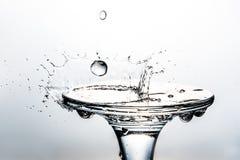 Вода падения падения конца-вверх в форме кроны разделена на стекле на предпосылке Стоковое Изображение