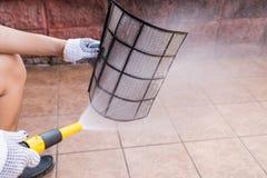 Вода персоны распыляя на фильтр кондиционера воздуха для того чтобы очистить пыль стоковые фото
