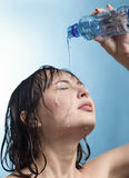 Вода питья девушки красоты от пластичной бутылки на голубой предпосылке Стоковые Изображения