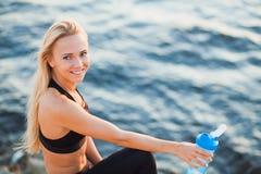 Вода питья женщины красивой блондинкы подходящая на скалистом пляже от шейкера Стоковые Изображения RF