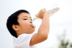 Вода питья мальчика от бутылки Стоковое Изображение RF