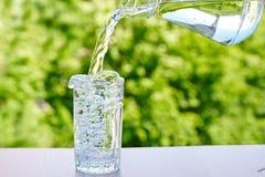 Вода полита от кувшина в стекло стоковые фотографии rf
