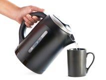 Вода современного чайника лить в чашку изолированную на белизне стоковые фотографии rf