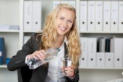 Вода счастливой коммерсантки лить в стекле Стоковое Изображение
