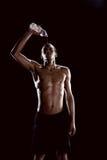 Вода Sporty африканского человека лить на стороне на черноте стоковое фото