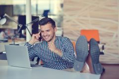 Во всю длину расслабленного вскользь молодого бизнесмена сидя с ногами на столе на офисе стоковая фотография rf