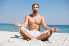 Во всю длину без рубашки человека размышляя на пляже стоковая фотография