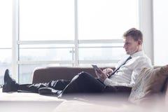 Во всю длину бизнесмена используя цифровую таблетку на софе дома Стоковое фото RF