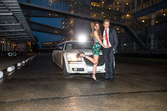 Во всю длину блестящих молодых пар стоя перед limou Стоковое Изображение RF