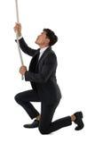 Во всю длину веревочки бизнесмена вытягивая пока встающ на колени Стоковые Изображения