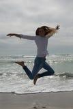 Во всю длину вскользь женщины скача на пляж Стоковое Фото