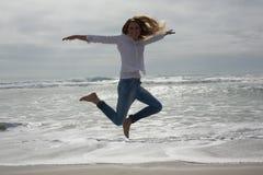 Во всю длину вскользь женщины скача на пляж Стоковые Фотографии RF